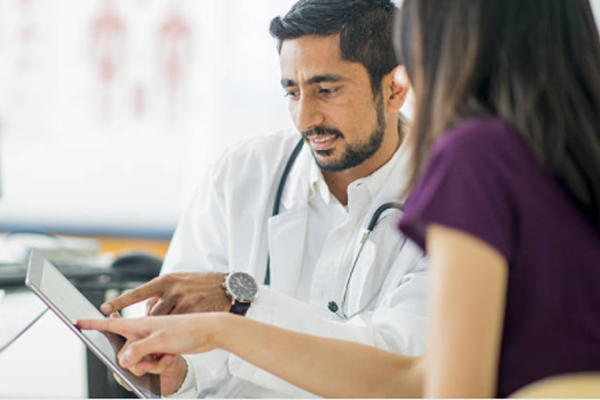 Young dentist with a black beard sharing information from a tablet with a young woman