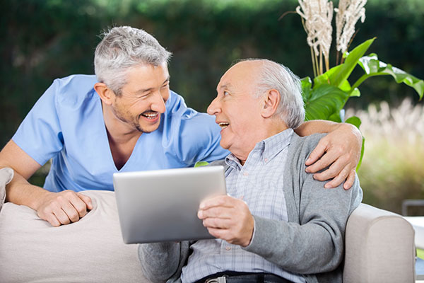 An older man sitting on a couch while holding an iPad and looking at the dentist who is smiling with his arm around the man