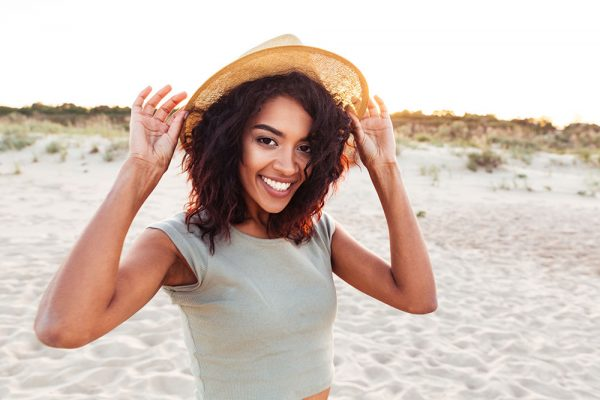 Woman with a hat smiling while standing on the beach