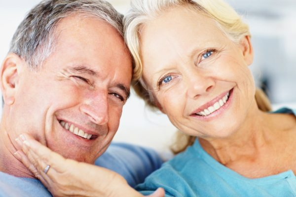 closeup of an older couple smiling and leaning their heads against each other